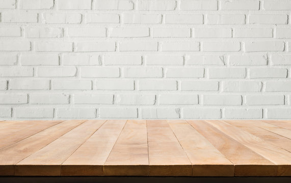 Empty wood table top with white brick wall background.