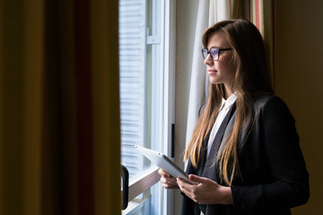 Young beautiful woman in formal suit holding tablet and looking thoughtfully away in window.