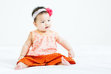 Portrait of adorable baby sitting on a white floor  with head band