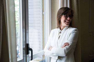Beautiful woman in formal white suit and eyeglasses standing with hands crossed laughing away.