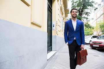 Young businessman in trendy suit walking down street looking away and holding briefcase.