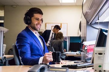 Handsome businessman with coffee wearing headset and working with computer in office.