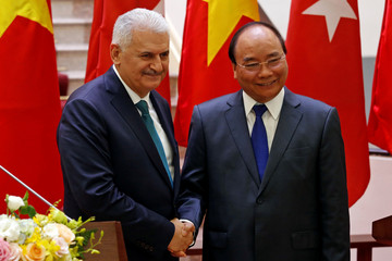 Turkish Prime Minister Binali Yildirim shakes hands with his Vietnamese counterpart Nguyen Xuan Phuc after attending a press briefing at the Government Office in Hanoi