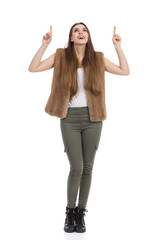 Woman In Fur Vest Looking Up And Pointing
