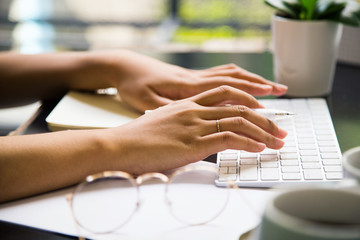 Typing and working on the table at workplace