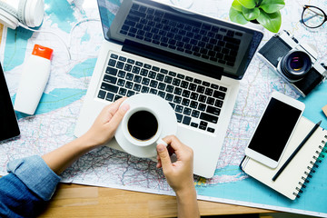 Laptop coffee and accessory on map at office