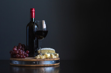 Bottle and glass with red wine near cheese composition on a wooden board