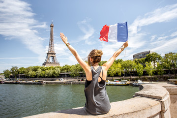 Young stylish woman with french flag enjoying great view on the Eiffel tower sitting back on the bridge in Paris