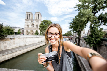 Young woman tourist making selfie portrait in front of the famous Notre Dame cathedral in Paris