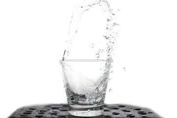 Pour water fresh into glass against the nature in shape water splash isolated on white background .
