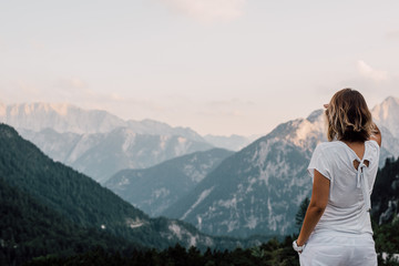 Woman sitting on a and enjoying beautiful landscape/ mountain and clouds