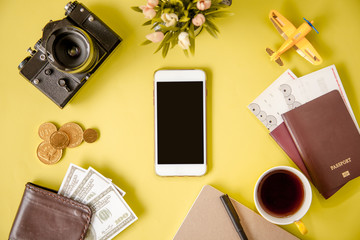 Modern mobile smart phone on table desktop Mix for preparations before the departure of the tourists with has smart Phone,camera,coffee mug,diary,pocket money,passport On table desk.concept of tourism