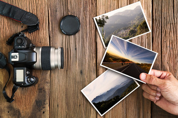 Man's hand holding photo with old grunge camera and photos on vintage grunge wooden background, vocation photography concept