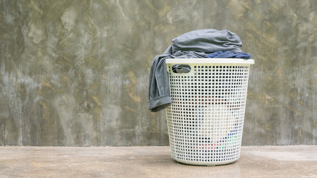 Gray clothes in a white hamper on a cement background.