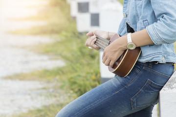 Asian young wonmen hug her ukulele