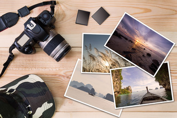 Old camera, cap, memory cards  and stack of photos on wooden background, photography hobby lifestyle concept