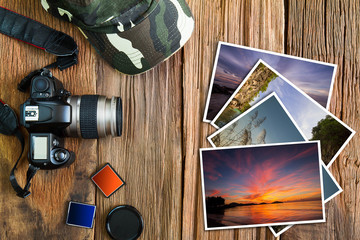 Old camera, cap, memory cards  and stack of photos on vintage wooden background, photography hobby lifestyle concept