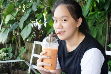 drinking thai tea or iced tea.
