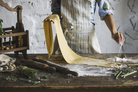 Young woman in the apron preparing the dough for homemade pasta at rustic kitchen