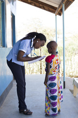 Nurse examing young girl in clinic. Kenya, Africa.