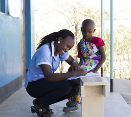 Nurse examining young girl in clinic. Kenya, Africa