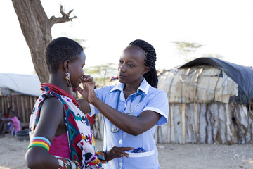 Nurse examing patient in rural village location. Kenya, Africa.
