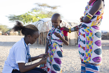Nurse examing young girl in rural village. Kenya, Africa.