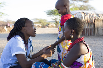 Nurse examing Mother and Daughter in rural village. Kenya, Africa.