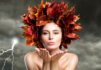 Autumn Woman Blowing Kiss on Cloudy Sky. Beautiful Fashion Model with Fall Leaves, Autumn Season Concept