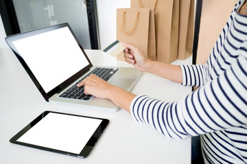 Closeup of happy young woman holding credit card inputting card information while and using laptop computer at home. Online shopping concept.