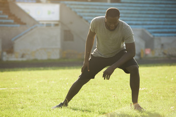 A handsome black man is performing stretching exersises for legs in the field