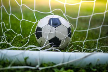 classic vintage soccer ball in goal net on green grass