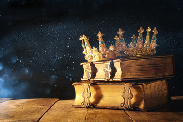low key of queen/king crown on old books. vintage filtered. fantasy medieval period