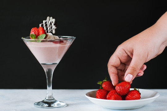 Young woman taking strawberry from little saucer. Sweet fruit souffle in martini glass and fresh red berries nearby as concept of seduction, close up picture