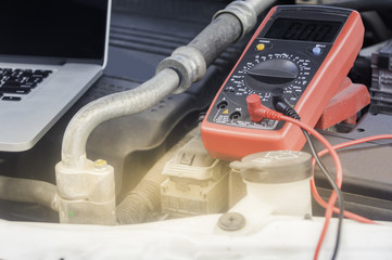 Auto mechanic uses a multimeter voltmeter to check the voltage level in a car battery.