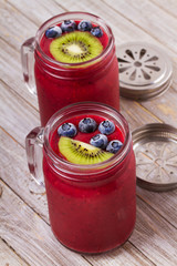 Berry kiwi smoothie in the jars, garnished with blueberries and kiwi