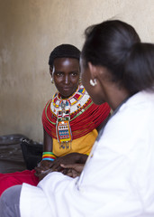 Female Doctor examing woman from Samburu tribe. Kenya, Africa.