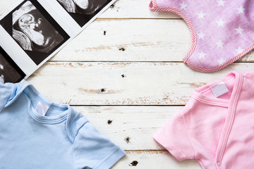 Pink and blue baby romper and ultrasound on white wooden background.Copyspace