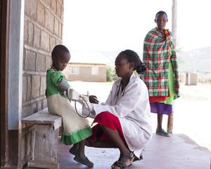 Female Doctor taking blood pressure of child (girl). Kenya, Africa.