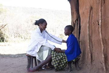 Female Doctor examining female Maasai patient in Maasai village. Kenya, Africa.