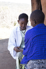 Female Doctor examing Maasai patient, in Maasai village. Kenya, Africa.