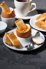 soft boiled egg, toasts and cup of coffee for breakfast on dark background, vertical