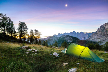 A tent glows under a moon night sky at twilight hour. Alps, Triglav National Park, Slovenia.