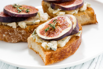 toast with figs and blue cheese on a plate, closeup