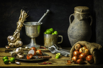 still life with fresh organic onions placed with garlic,lemon,dry cayenne on rustic wooden background
