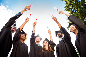 Six excited successful graduates in black robes are looking at the certificates in their raised up hands. They did it, passed exams, finished course of studies, got the degree