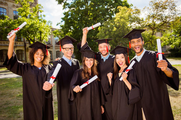 Triumph, education, graduation and people concept - group of happy six international students in mortar boards and bachelor gowns with diplomas,  celebrating success