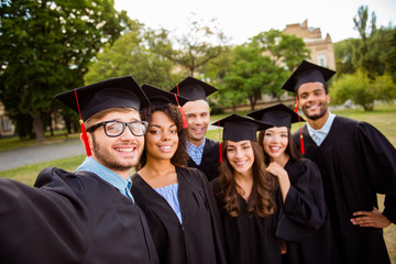 Selfie time! Six international students are posing for selfie shot, that nerdy guy is taking, outside school building. Gathered, cheerful, smart and successful youth in mortar boards, gowns