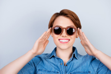 Close up photo of funny smiling young woman in casual clothes touching her stylish sunglasses