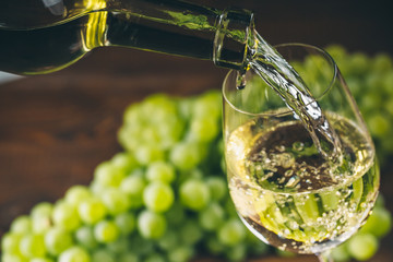 Pouring white wine into a glass with a bunch of green grapes against wooden background